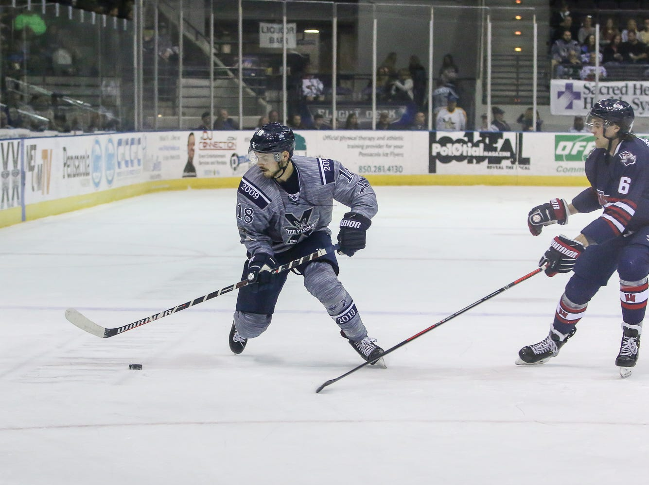 Pensacola's Andrew Schmit (18) makes a quick move to keep Macon's Zach Urban (6) from the puck during the last home game of the regular season at the Pensacola Bay Center on Saturday, March 23, 2019. With over 4,300 people in attendance for Pensacola's 3-1 victory, the Ice Flyers mark six straight years of over 100,000 people at their home games each season. The team has won their last five games in a row and will finish out their last five games on the road before entering the playoffs in a couple of weeks.