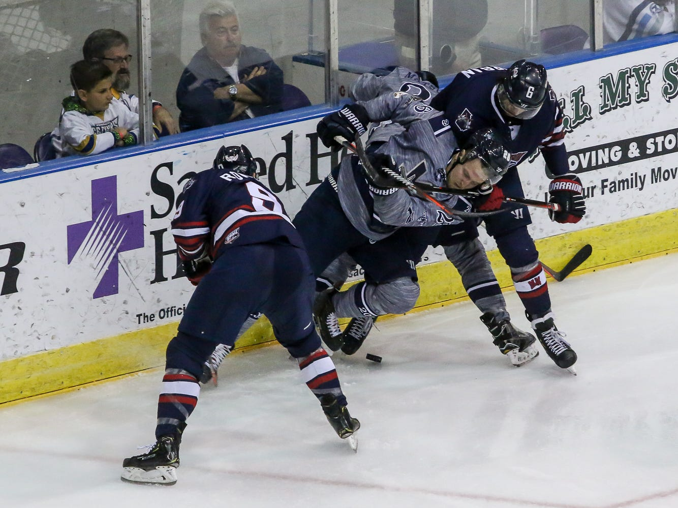 Pensacola's Brian Morgan (26) gets tripped up as he battles for control of the puck against Macon's Zach Urban (6) during the last home game of the regular season at the Pensacola Bay Center on Saturday, March 23, 2019. With over 4,300 people in attendance for Pensacola's 3-1 victory, the Ice Flyers mark six straight years of over 100,000 people at their home games each season. The team has won their last five games in a row and will finish out their last five games on the road before entering the playoffs in a couple of weeks.