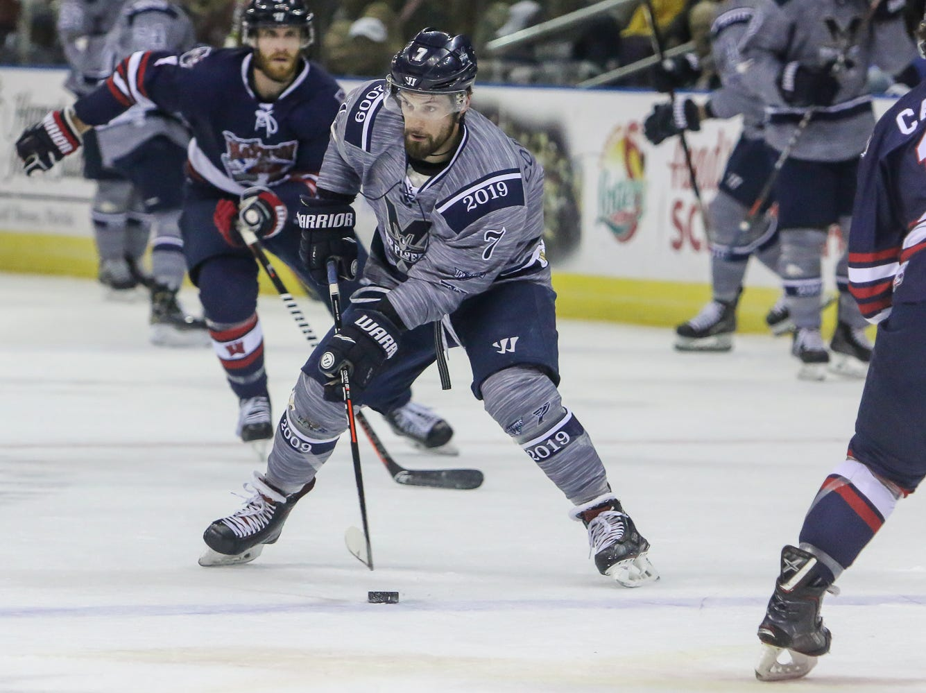 Pensacola's Josh Cousineau (7) slips the puck past the Macon defenders during the last home game of the regular season at the Pensacola Bay Center on Saturday, March 23, 2019. With over 4,300 people in attendance for Pensacola's 3-1 victory, the Ice Flyers mark six straight years of over 100,000 people at their home games each season. The team has won their last five games in a row and will finish out their last five games on the road before entering the playoffs in a couple of weeks.