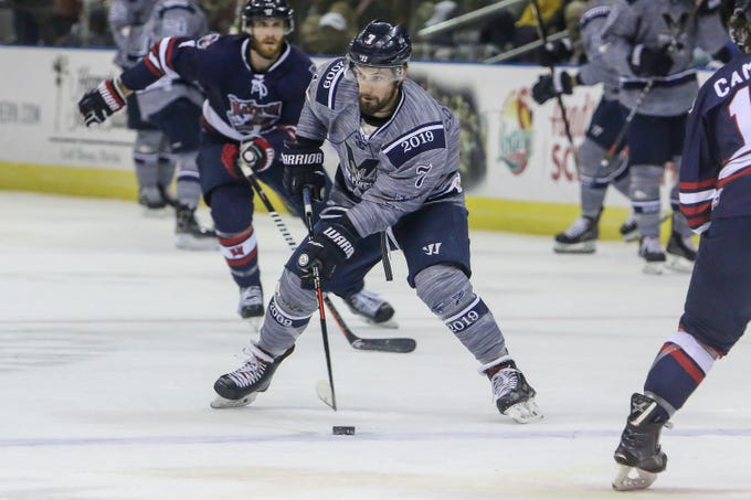 Pensacola s Josh Cousineau (7) slips the puck past the Macon defenders  during the last 529b17428