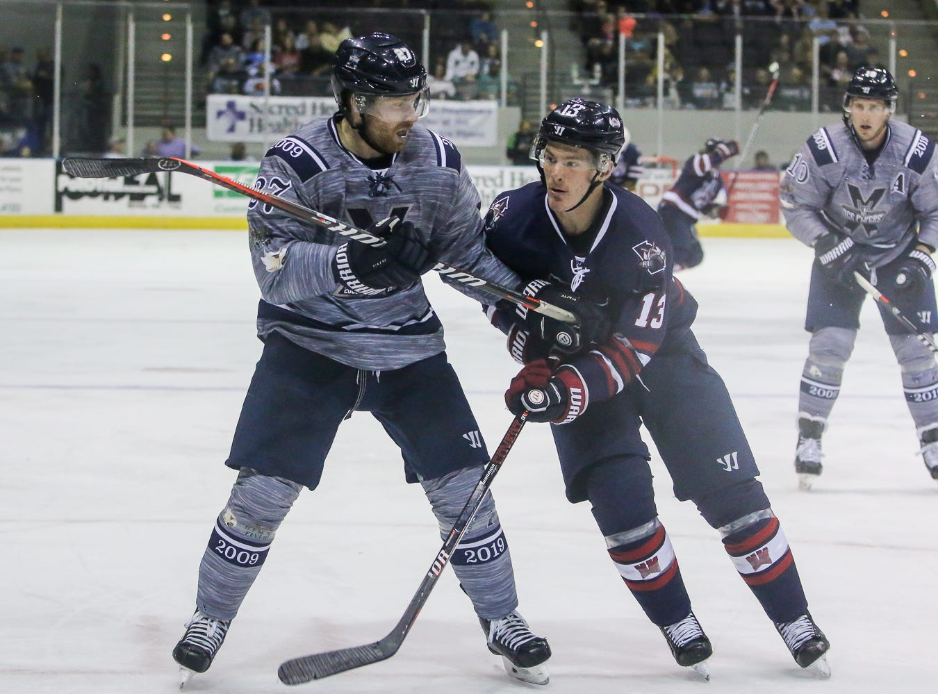 Pensacola's Jesse Kessler (27) keeps Macon's Jimmy Soper (13) from getting to the loose puck during the last home game of the regular season at the Pensacola Bay Center on Saturday, March 23, 2019. With over 4,300 people in attendance for Pensacola's 3-1 victory, the Ice Flyers mark six straight years of over 100,000 people at their home games each season. The team has won their last five games in a row and will finish out their last five games on the road before entering the playoffs in a couple of weeks.