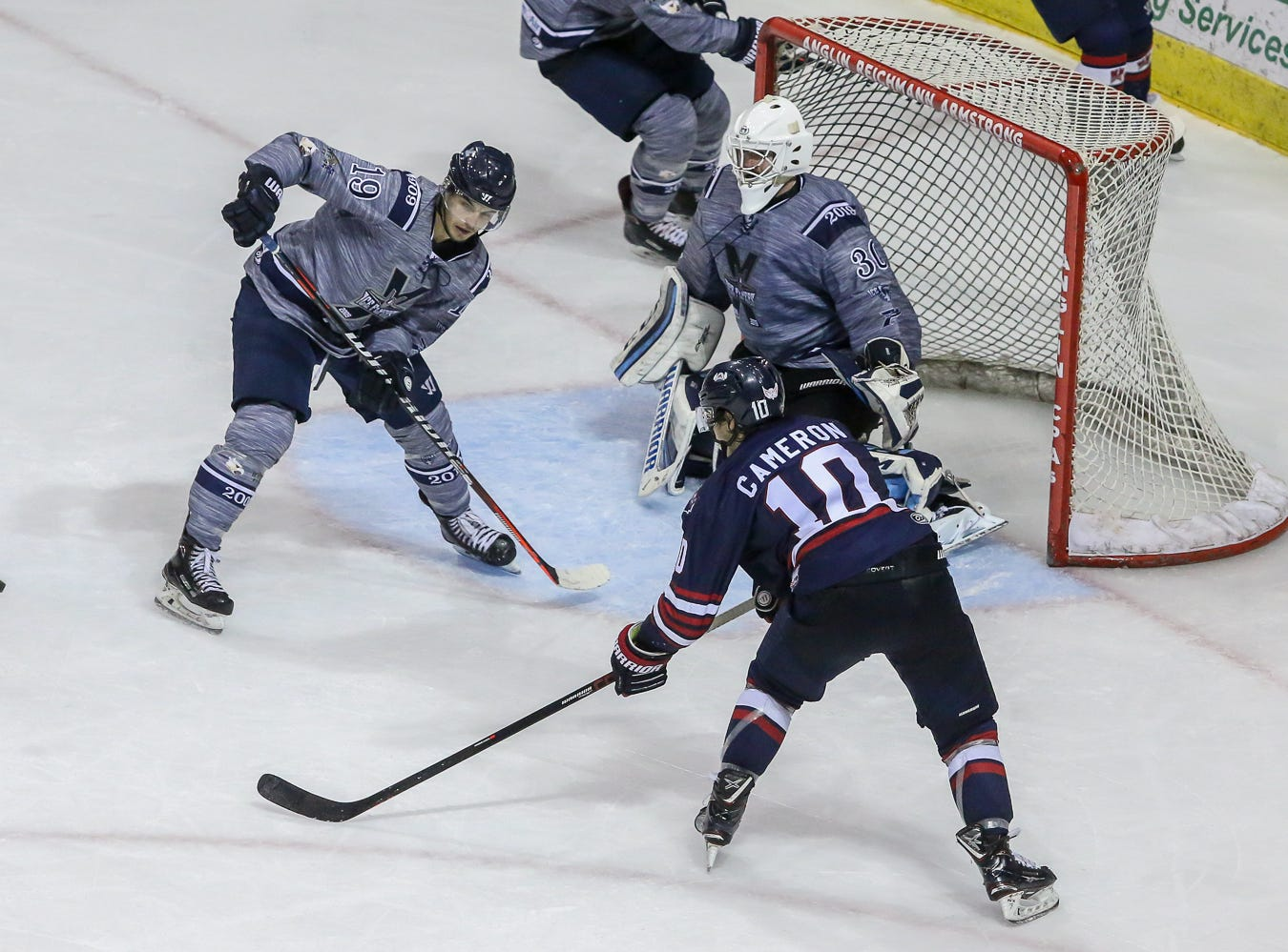 Pensacola's Brett D'Andrea (19) and Macon's Caleb Cameron (10) watch as the puck flies away from the net after goaltender Brian Billett (30) deflected it during the last home game of the regular season at the Pensacola Bay Center on Saturday, March 23, 2019. With over 4,300 people in attendance for Pensacola's 3-1 victory, the Ice Flyers mark six straight years of over 100,000 people at their home games each season. The team has won their last five games in a row and will finish out their last five games on the road before entering the playoffs in a couple of weeks.