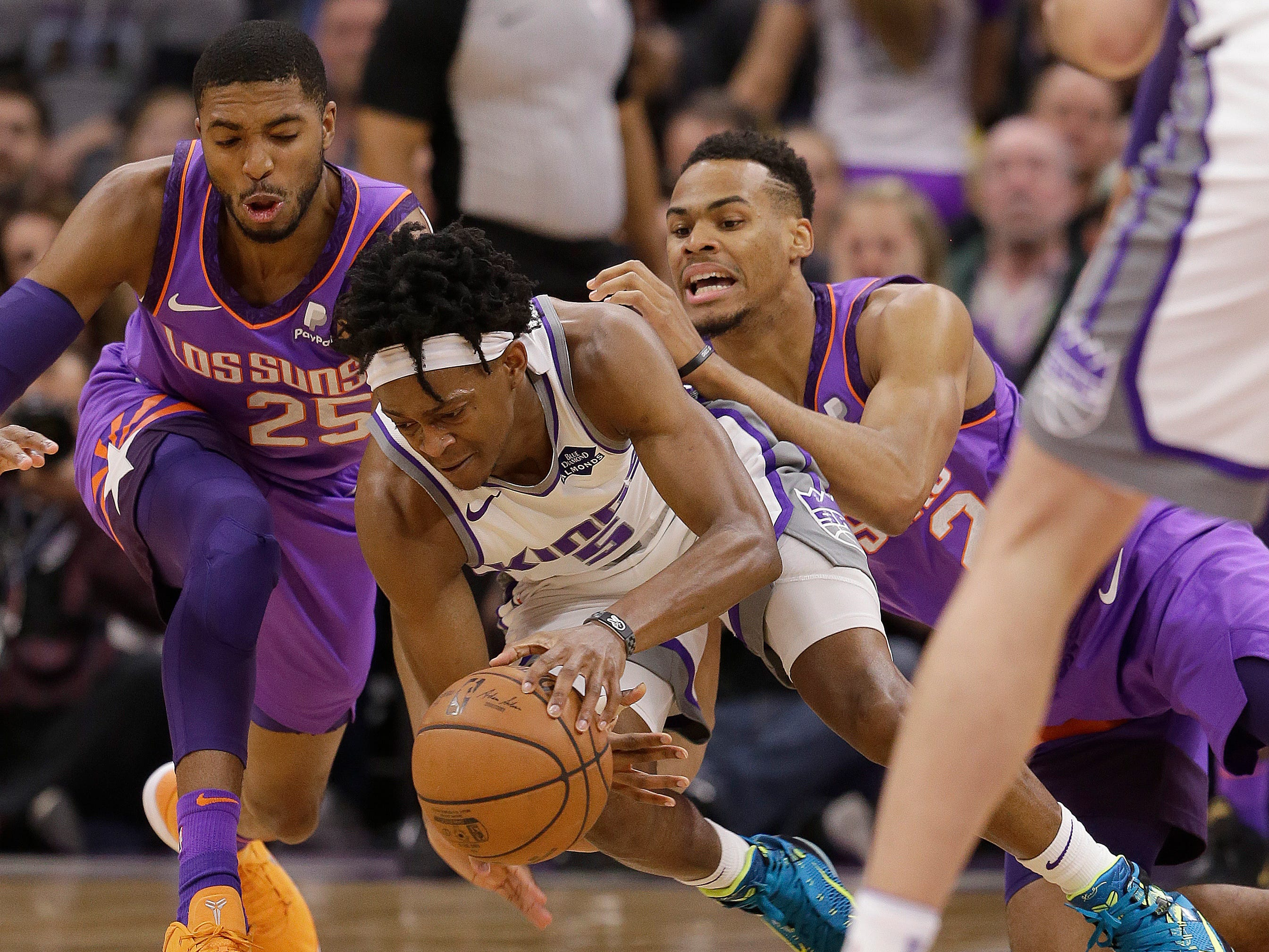 Sacramento Kings guard De'Aaron Fox, center, dives for the ball between Phoenix Suns' Mikal Bridges, left, and Elie Okobo during the first quarter of an NBA basketball game Saturday, March 23, 2019, in Sacramento, Calif.