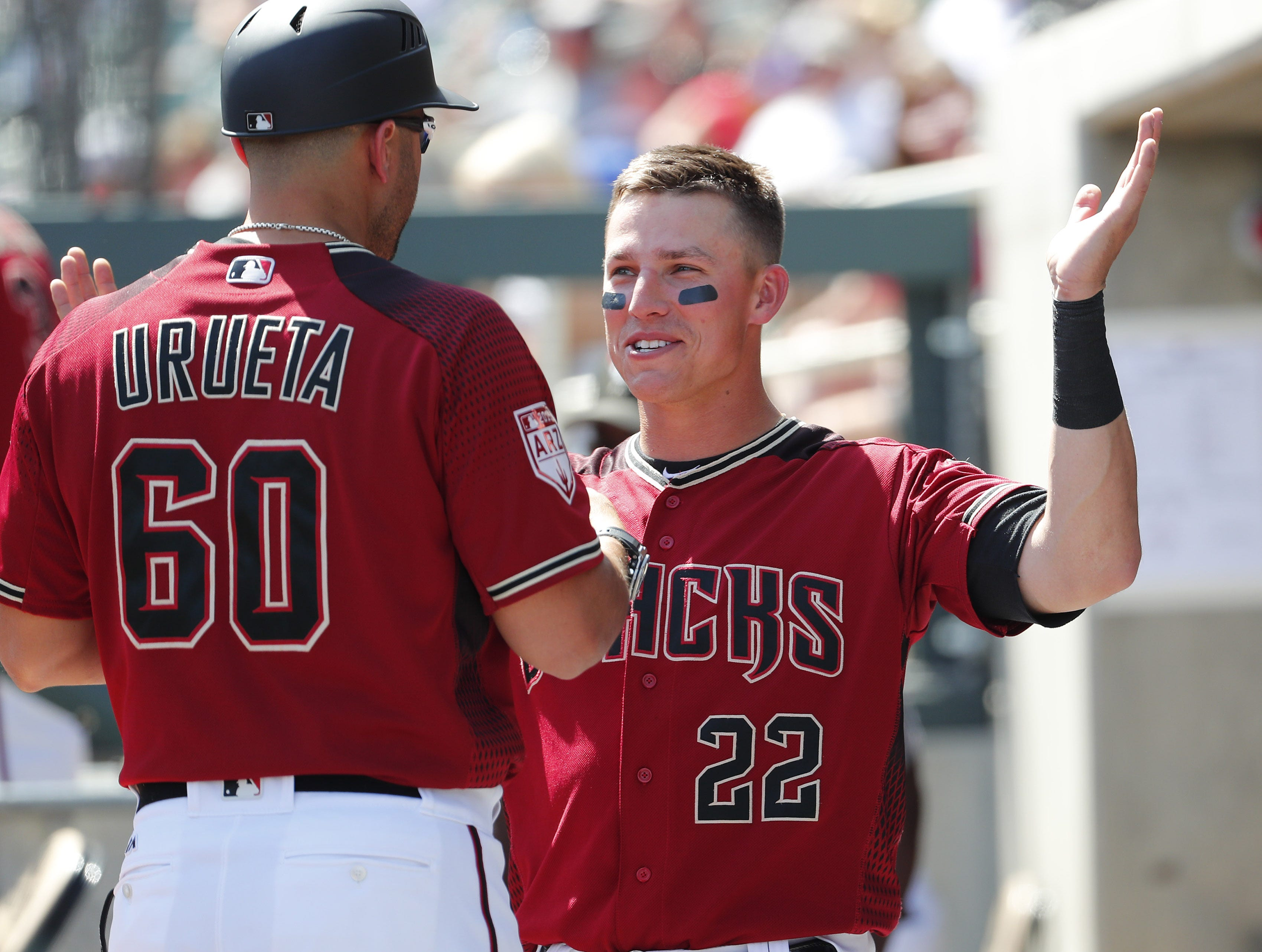 Arizona Diamondbacks first baseman Jake Lamb (22) talks with coach Luis Urueta (60) during a spring training game against the Milwaukee Brewers at Salt River Fields at Talking Stick March 24, 2019.