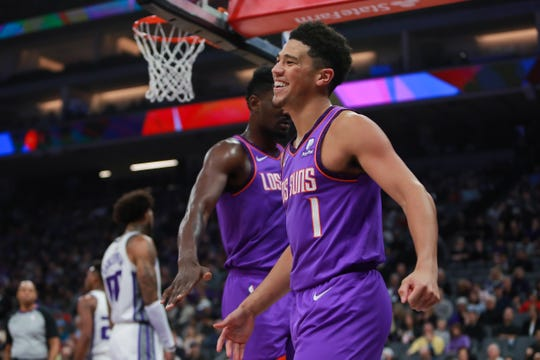 Mar 23, 2019; Sacramento, CA, USA; Phoenix Suns guard Devin Booker (1) is congratulated by center Deandre Ayton (22) after a play during the first quarter against the Sacramento Kings at Golden 1 Center.
