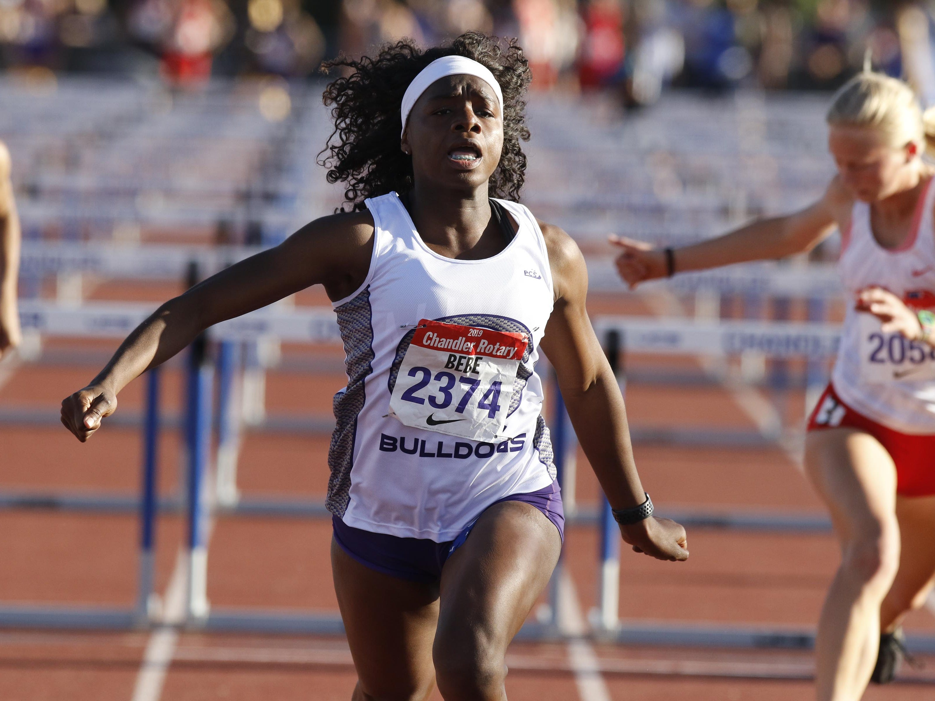 Queen Creek's Myreanna Bebe luges at the finish of the  110 Hurdles which she won with a time of 13.81 during the 79th Annual Nike Chandler Rotary Invitational  March 23, 2019.