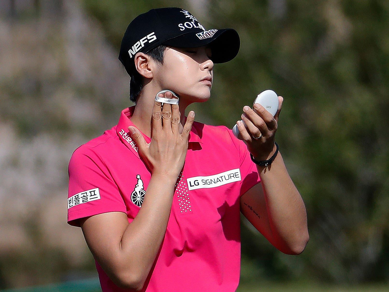 Sung Hyun Park applies sunscreen while on the eighth fairway during the third round of the Founders Cup LPGA golf tournament Saturday, March 23, 2019, in Phoenix.