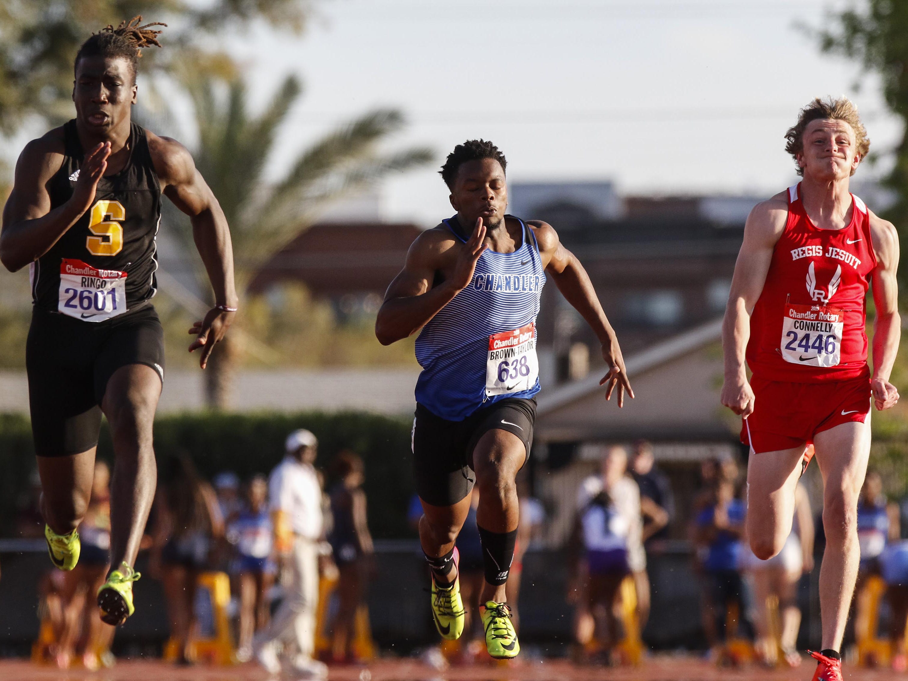 Saguaro's Kelee Ringo leads the 100 meters against Chandler's Quaron Adams and Jackson Connelly of Regis Jesuit during the 79th Annual Nike Chandler Rotary Invitational  March 23, 2019.