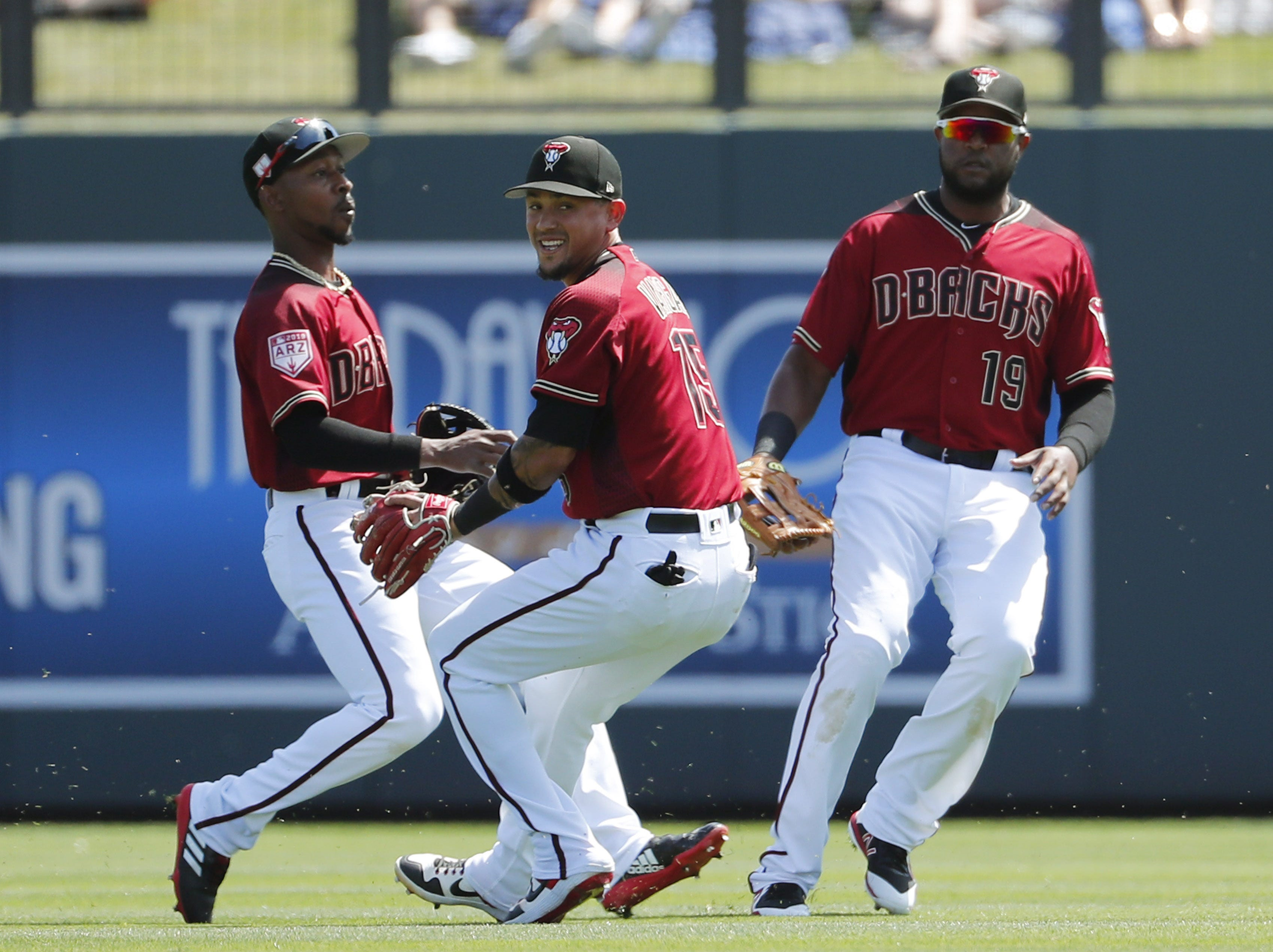 Arizona Diamondbacks second baseman Ildemaro Vargas (15) fields a ball between outfielders Jarrod Dyson (left) and Socrates Brito during spring training action against the Milwaukee Brewers at Salt River Fields at Talking Stick March 24, 2019.