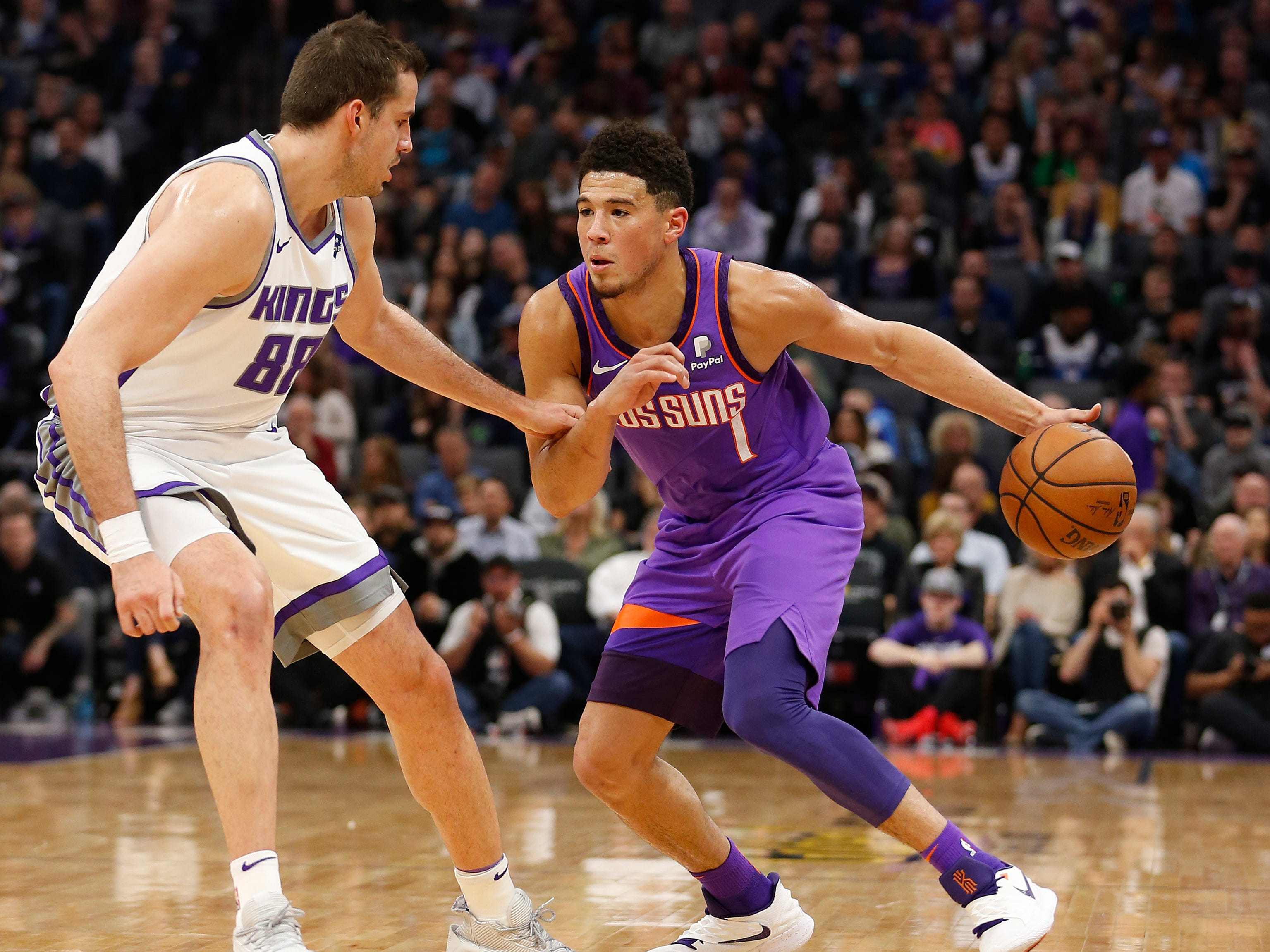 Phoenix Suns guard Devin Booker, right, drives against Sacramento Kings forward Nemanja Bjelica during the first quarter of an NBA basketball game Saturday, March 23, 2019, in Sacramento, Calif.