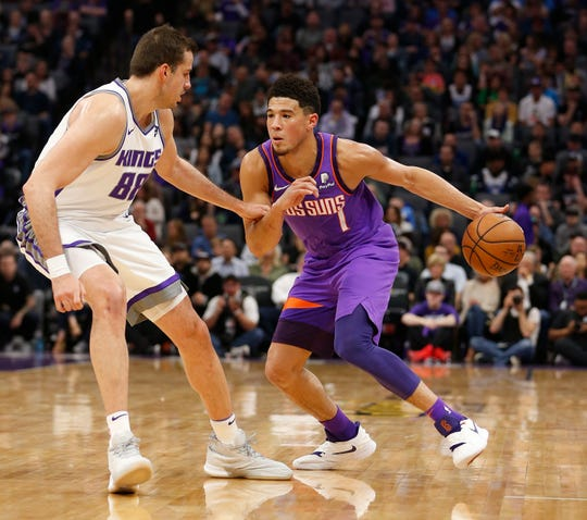 Devin Booker drives to the hoop against Kings forward Nemanja Bjelica during the first quarter of a game on March 23.