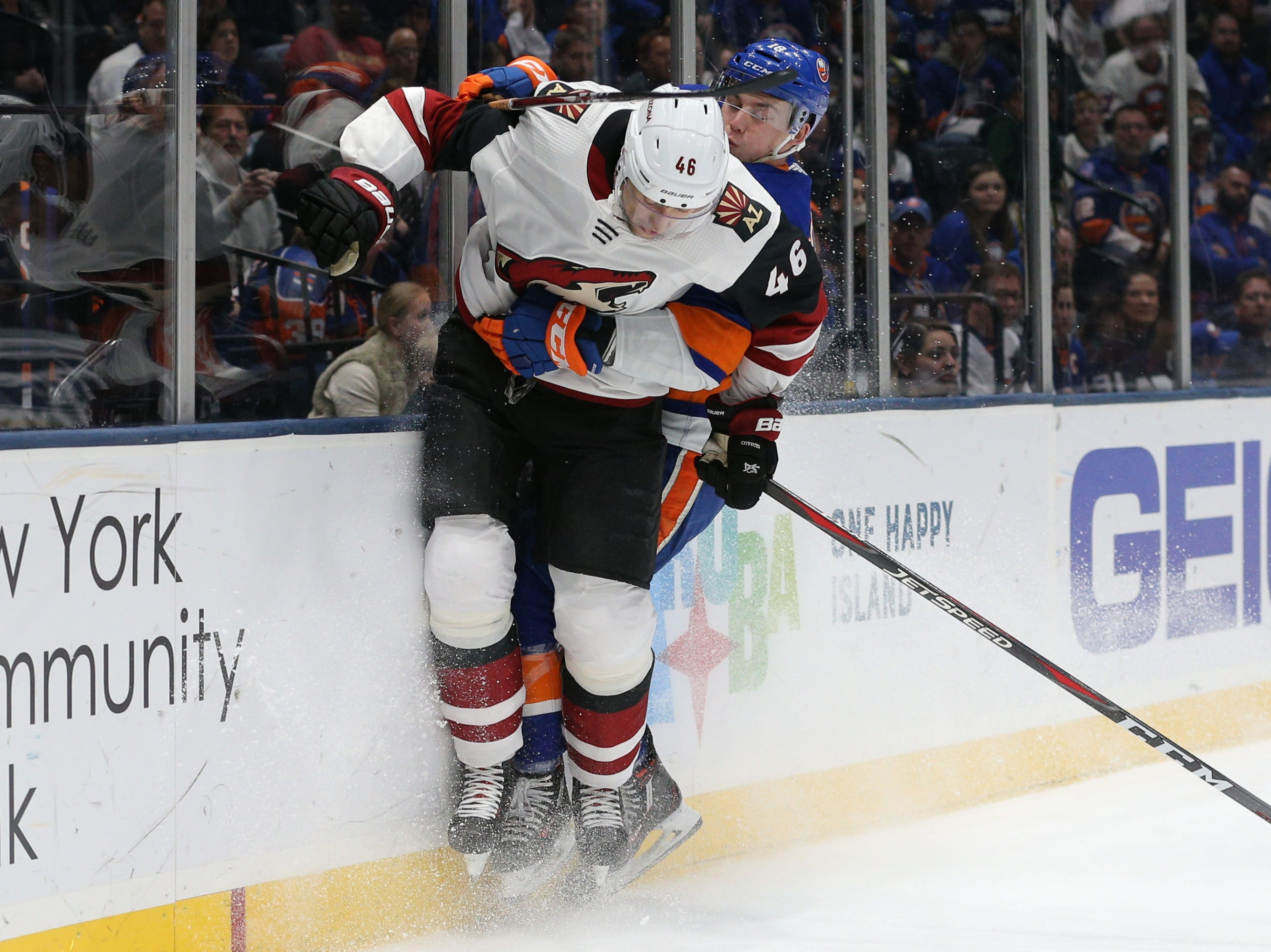 Mar 24, 2019; Uniondale, NY, USA; Arizona Coyotes defenseman Ilya Lyubushkin (46) and New York Islanders left wing Anthony Beauvillier (18) hit the boards during the second period at Nassau Veterans Memorial Coliseum. Mandatory Credit: Brad Penner-USA TODAY Sports