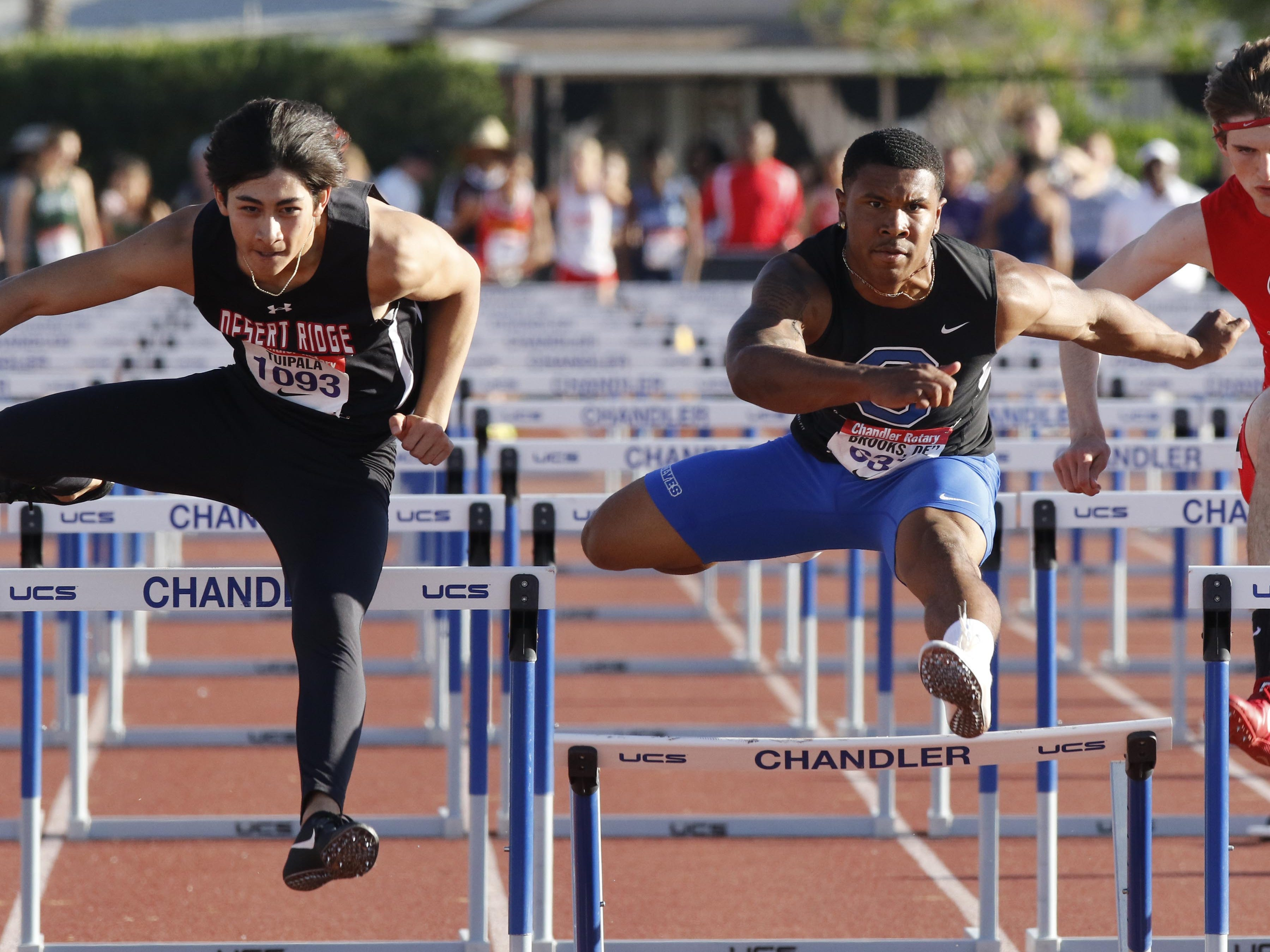 Desert Ridge's Koa Tuipala clears his hurdle while Chandlerr's DeCarlos Brooks clips his hurdle in the 110 Boy's High Hurdles during the 79th Annual Nike Chandler Rotary Invitational  March 23, 2019.  Tuipala won the event in 14.30 over Brooks' 14.31.