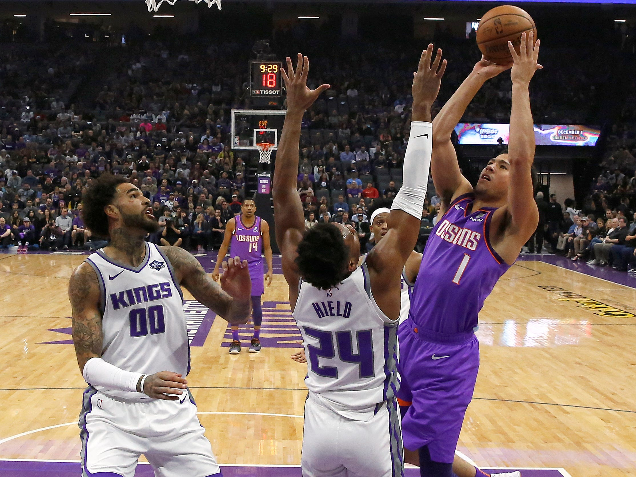Phoenix Suns guard Devin Booker, right, goes up for the shot against Sacramento Kings guard Buddy Hield, center, as Kings center Willie Cauley-Stein, left, watches during the first quarter of an NBA basketball game Saturday, March 23, 2019, in Sacramento, Calif.