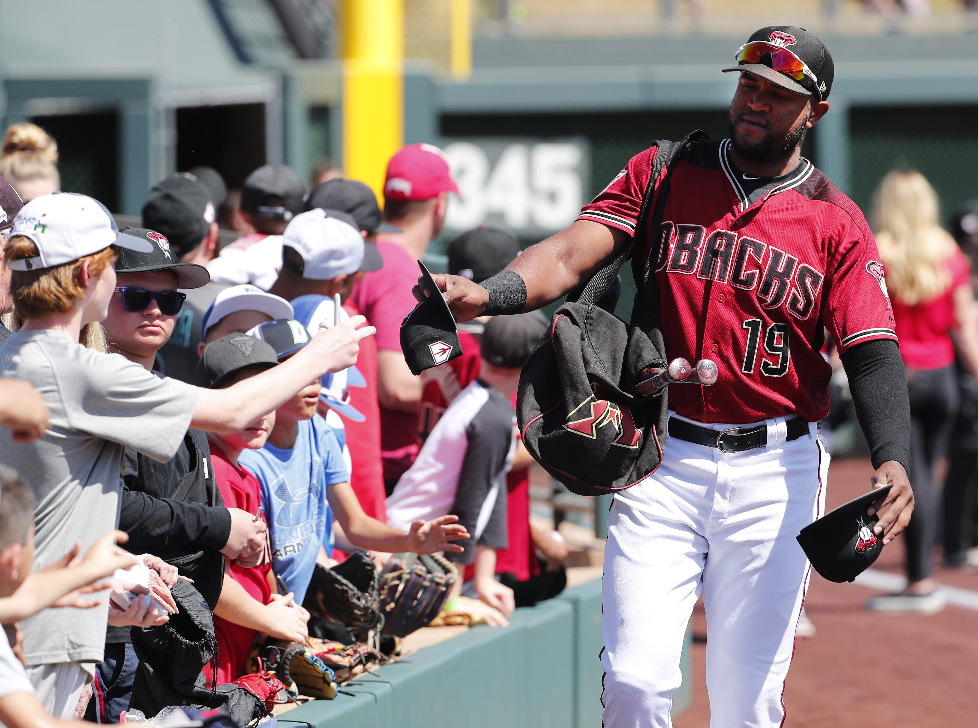 Arizona Diamondbacks center fielder Socrates Brito (19) hands out hats to fans before a spring training game against the Milwaukee Brewers at Salt River Fields at Talking Stick March 24, 2019.
