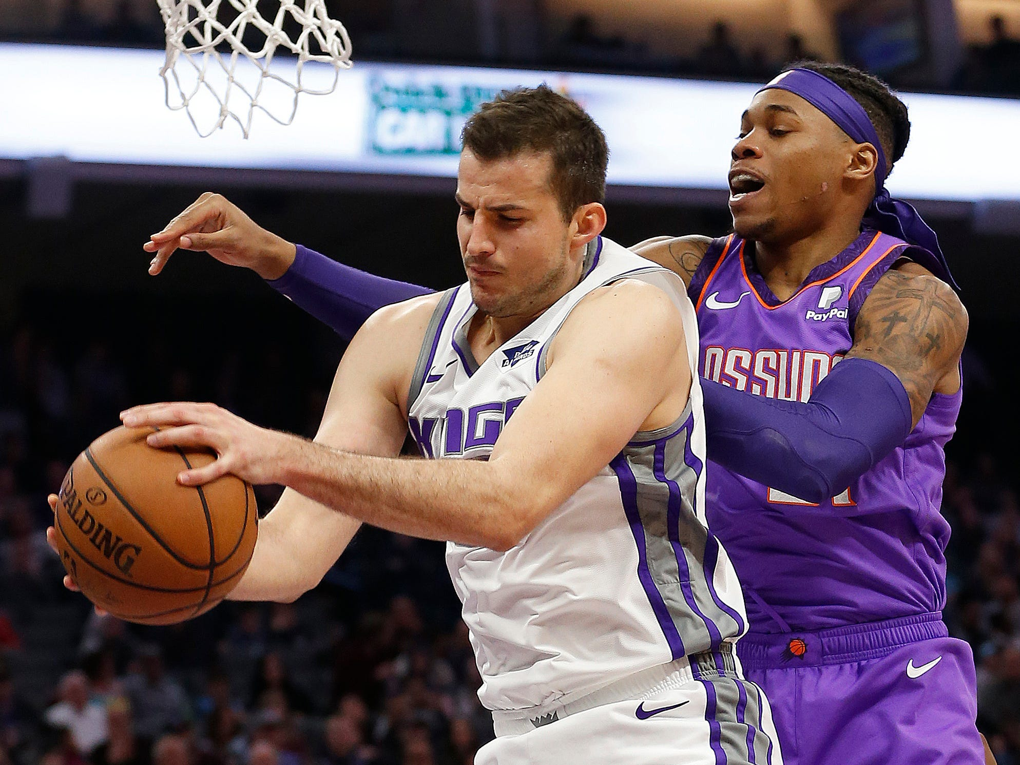 Sacramento Kings forward Nemanja Bjelica, left, grabs a rebound in front of Phoenix Suns forward Richaun Holmes during the first quarter of an NBA basketball game Saturday, March 23, 2019, in Sacramento, Calif.