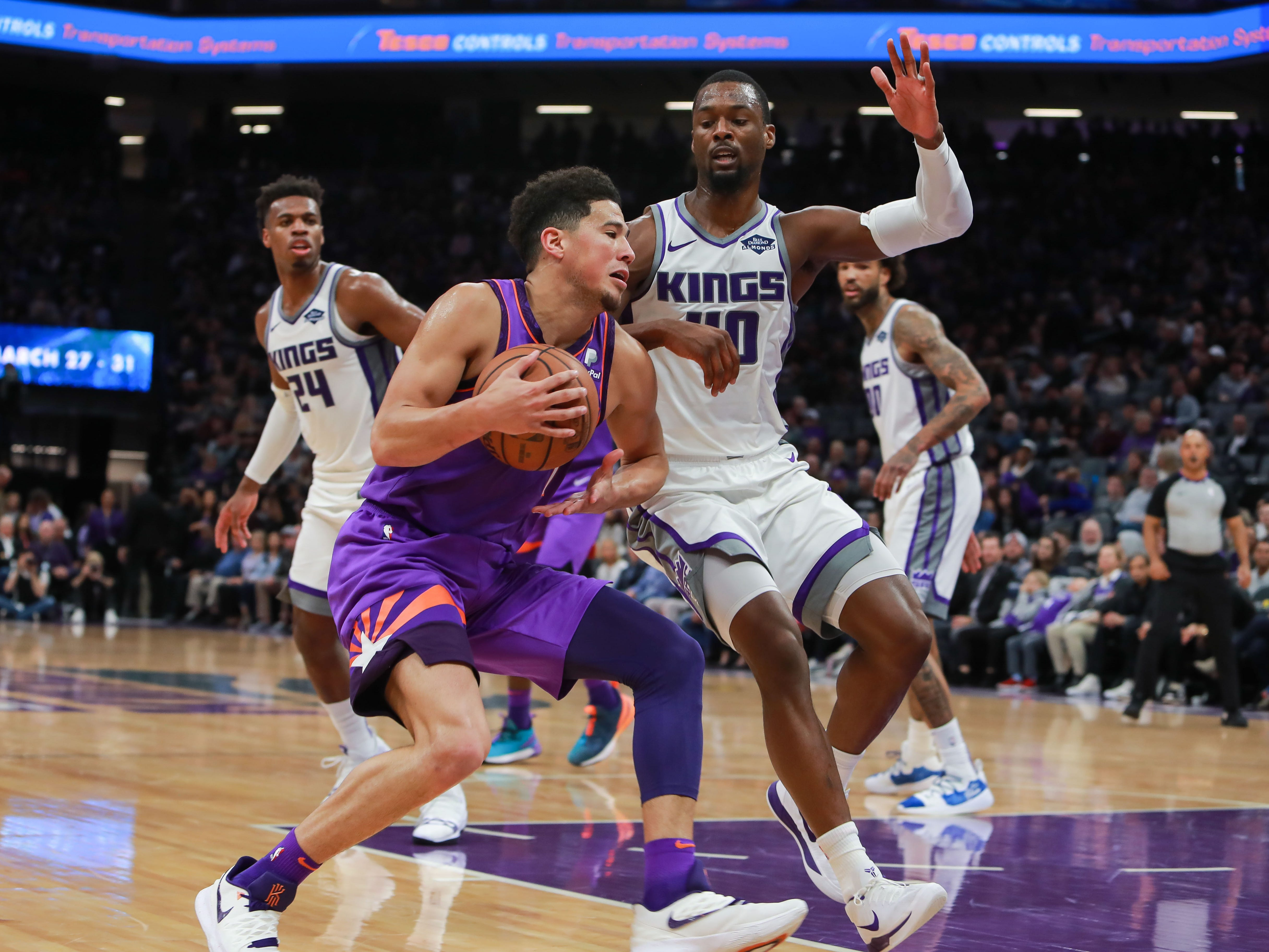 Mar 23, 2019; Sacramento, CA, USA; Phoenix Suns guard Devin Booker (1) dribbles the ball against Sacramento Kings forward Harrison Barnes (40) during the second quarter at Golden 1 Center.