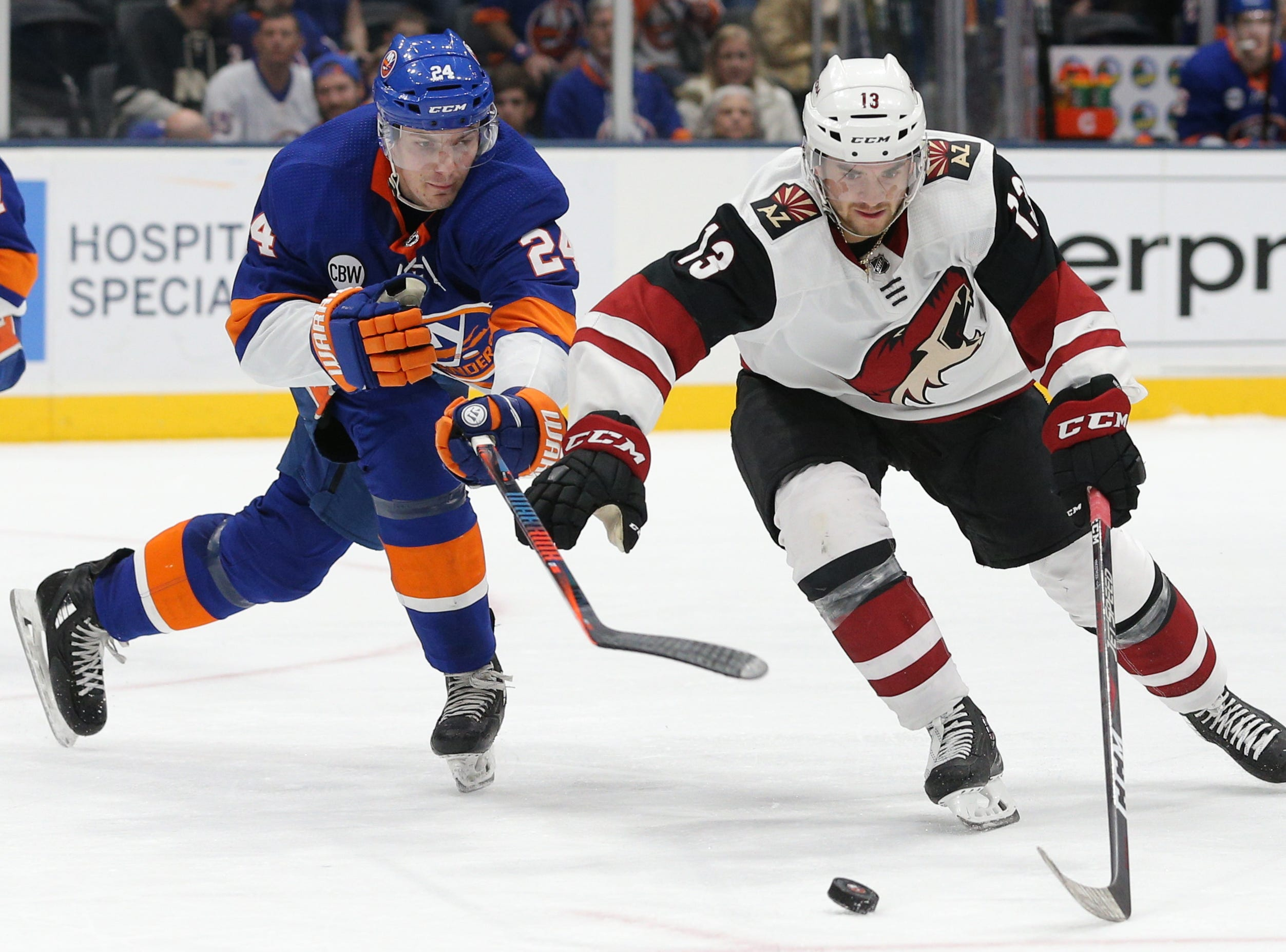 Mar 24, 2019; Uniondale, NY, USA; Arizona Coyotes center Vinnie Hinostroza (13) plays the puck against New York Islanders defenseman Scott Mayfield (24) during the third period at Nassau Veterans Memorial Coliseum. Mandatory Credit: Brad Penner-USA TODAY Sports