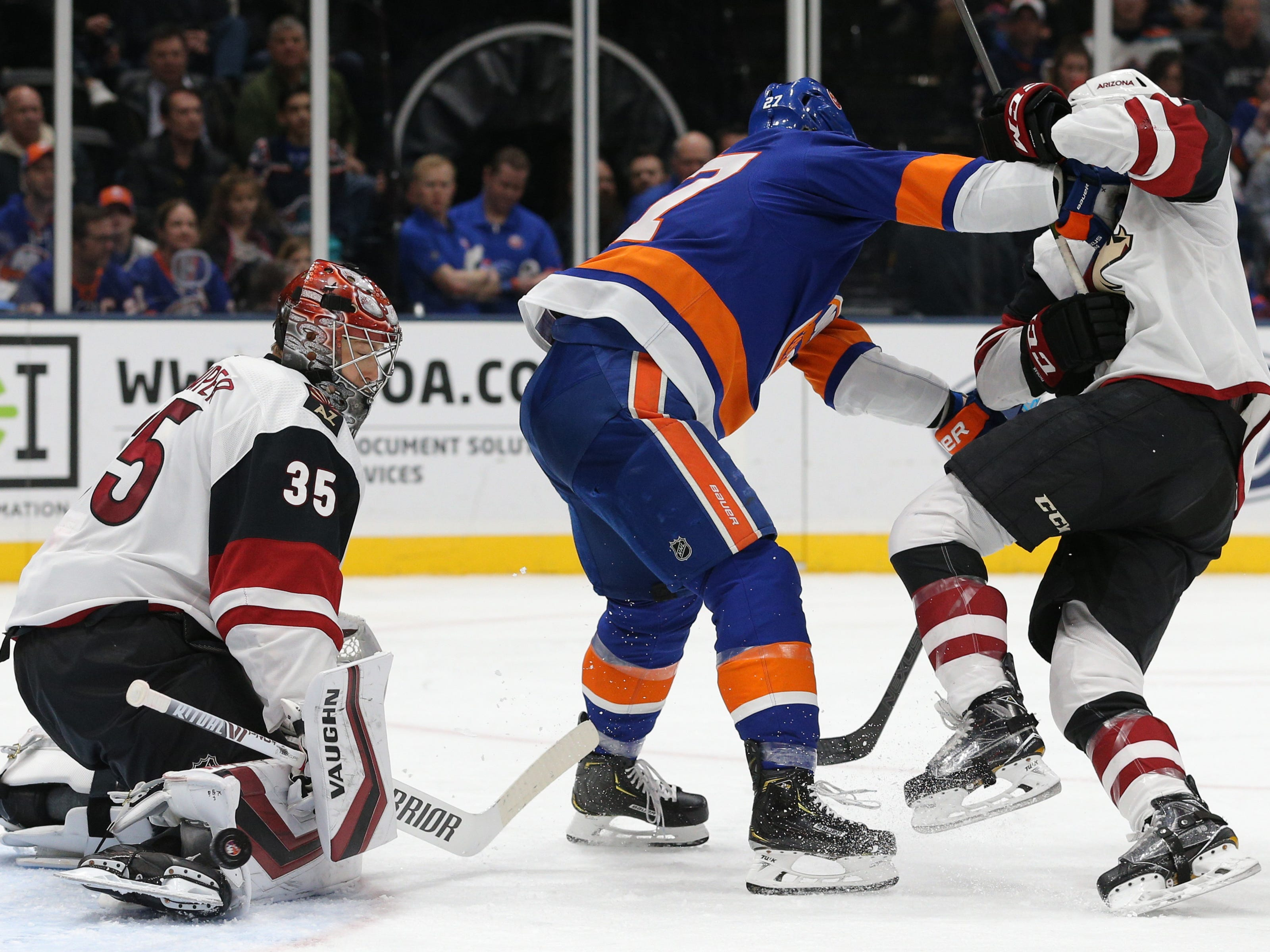 Mar 24, 2019; Uniondale, NY, USA; Arizona Coyotes goalie Darcy Kuemper (35) makes a save in front of New York Islanders left wing Anders Lee (27) during the second period at Nassau Veterans Memorial Coliseum. Mandatory Credit: Brad Penner-USA TODAY Sports
