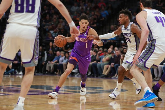 Mar 23, 2019; Sacramento, CA, USA; Phoenix Suns guard Devin Booker (1) dribbles the ball against Sacramento Kings guard Buddy Hield (24) during the second quarter at Golden 1 Center.
