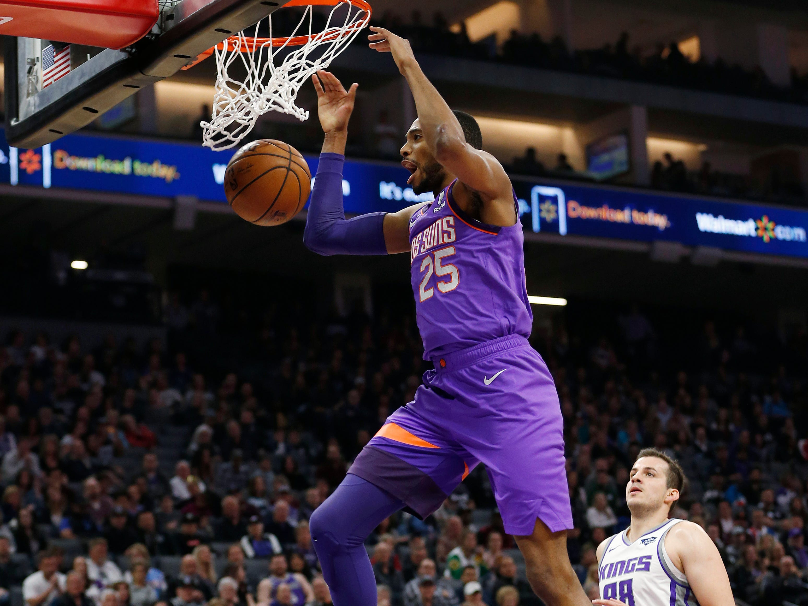 Phoenix Suns forward Mikal Bridges dunks as Sacramento Kings forward Nemanja Bjelica watches during the first quarter of an NBA basketball game Saturday, March 23, 2019, in Sacramento, Calif.