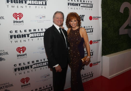 "Reba McEntire and Anthony ""Skeeter"" Lasuzzo pose for pictures during the Celebrity Fight Night red carpet in Scottsdale, Ariz., on March 23, 2019."