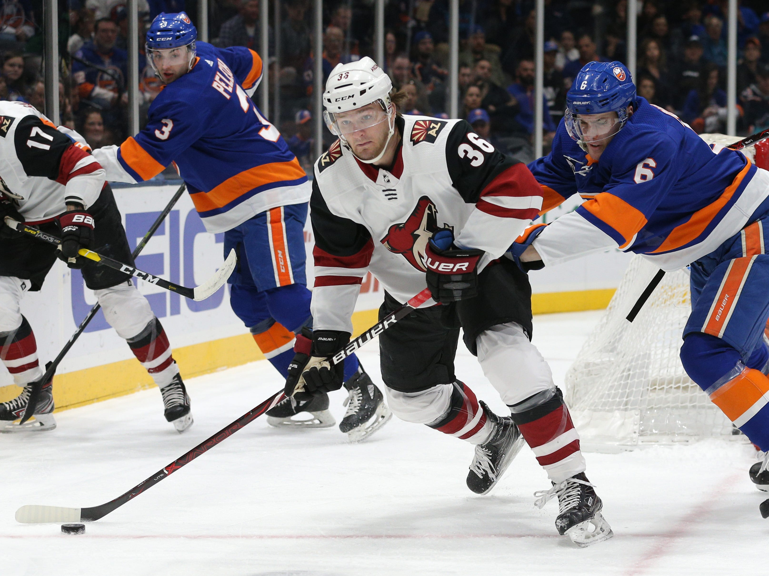Coyotes right wing Christian Fischer (36) looks to move the puck against Islanders defenseman Ryan Pulock (6) during the first period of a game at Nassau Veterans Memorial Coliseum.
