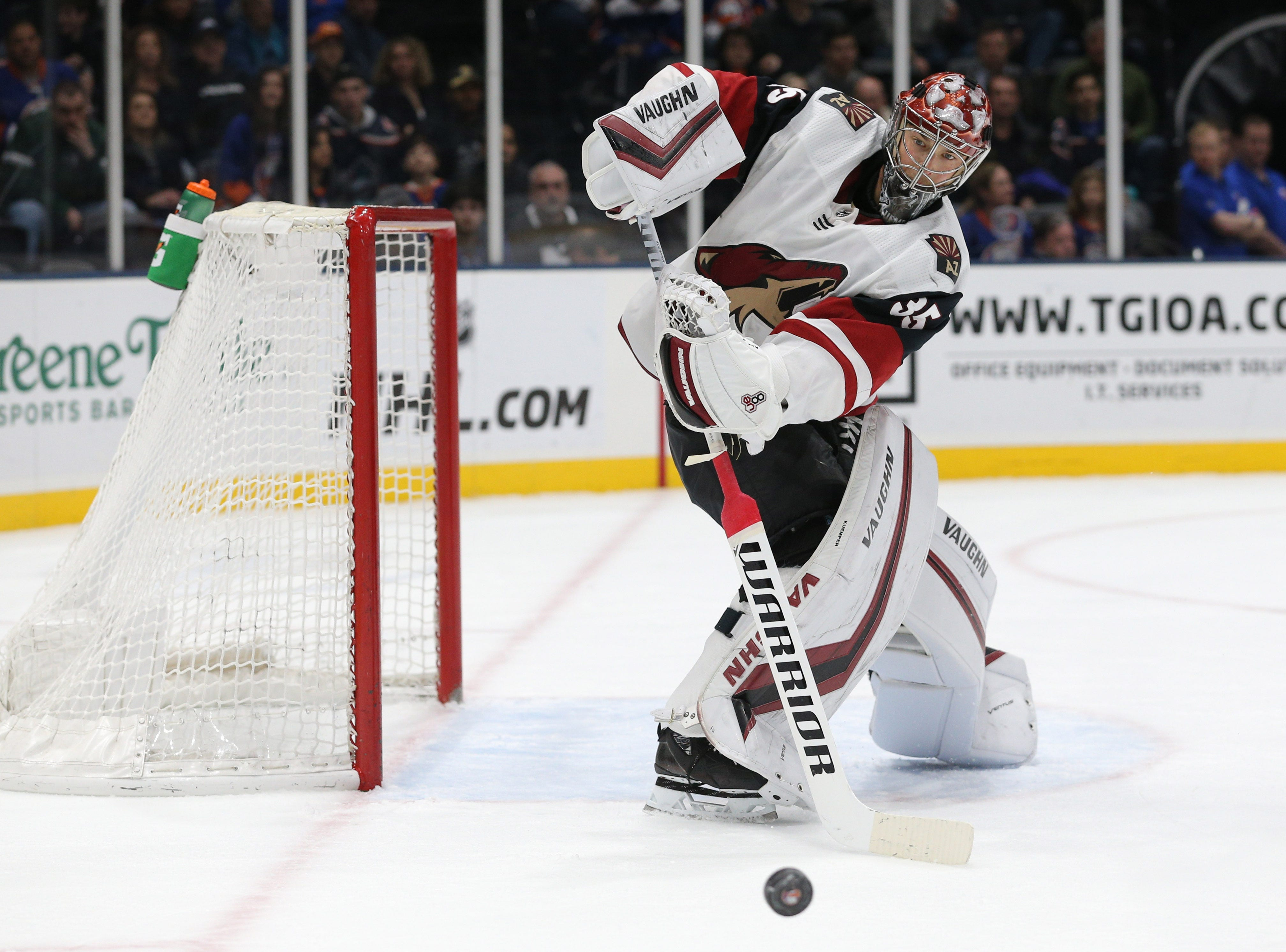 Mar 24, 2019; Uniondale, NY, USA; Arizona Coyotes goalie Darcy Kuemper (35) clears the puck from the crease against the New York Islanders during the second period at Nassau Veterans Memorial Coliseum. Mandatory Credit: Brad Penner-USA TODAY Sports