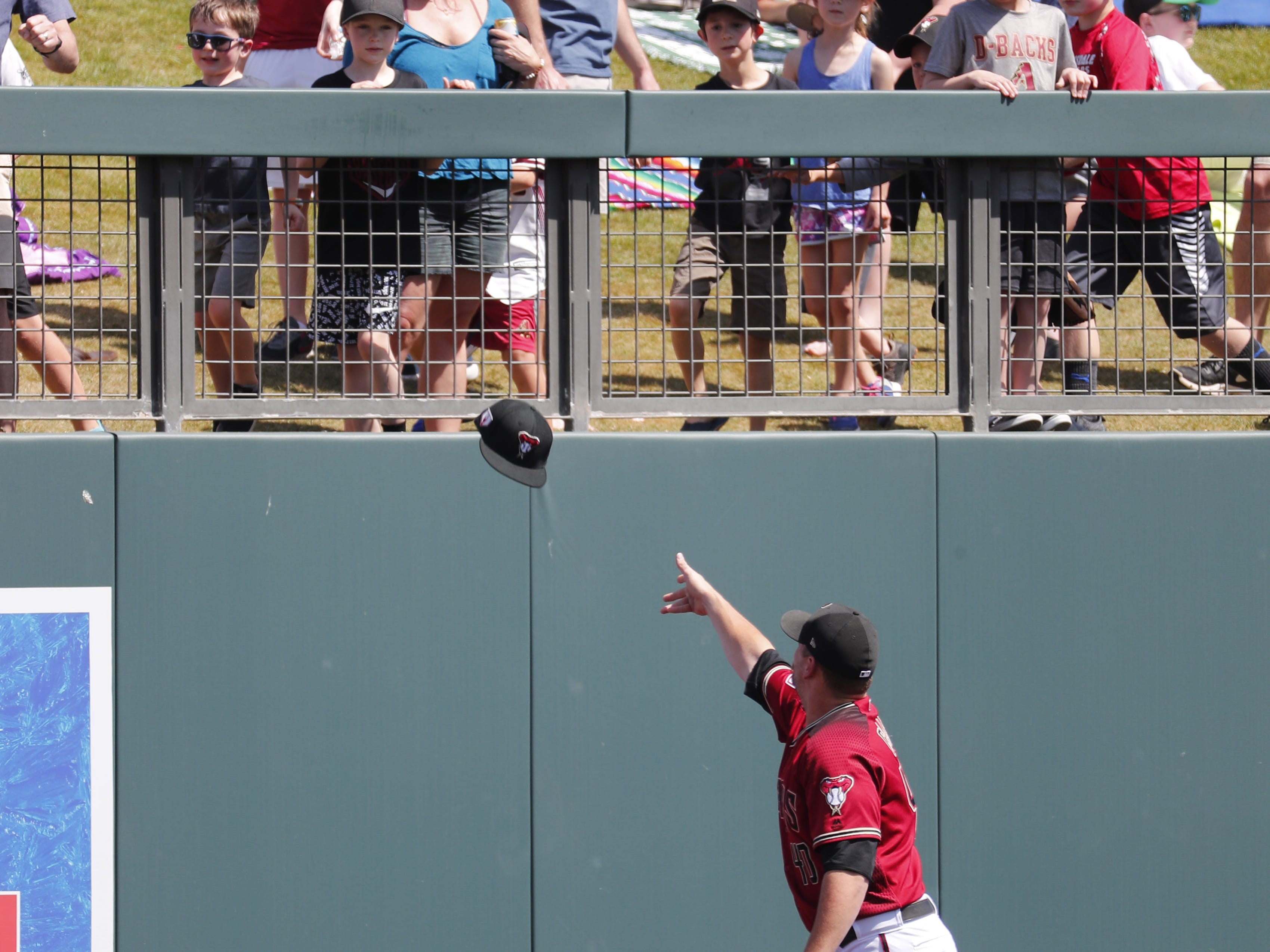 Arizona Diamondbacks relief pitcher Andrew Chafin (40) passes out hats to fans before a spring training game against the Milwaukee Brewers at Salt River Fields at Talking Stick March 24, 2019.