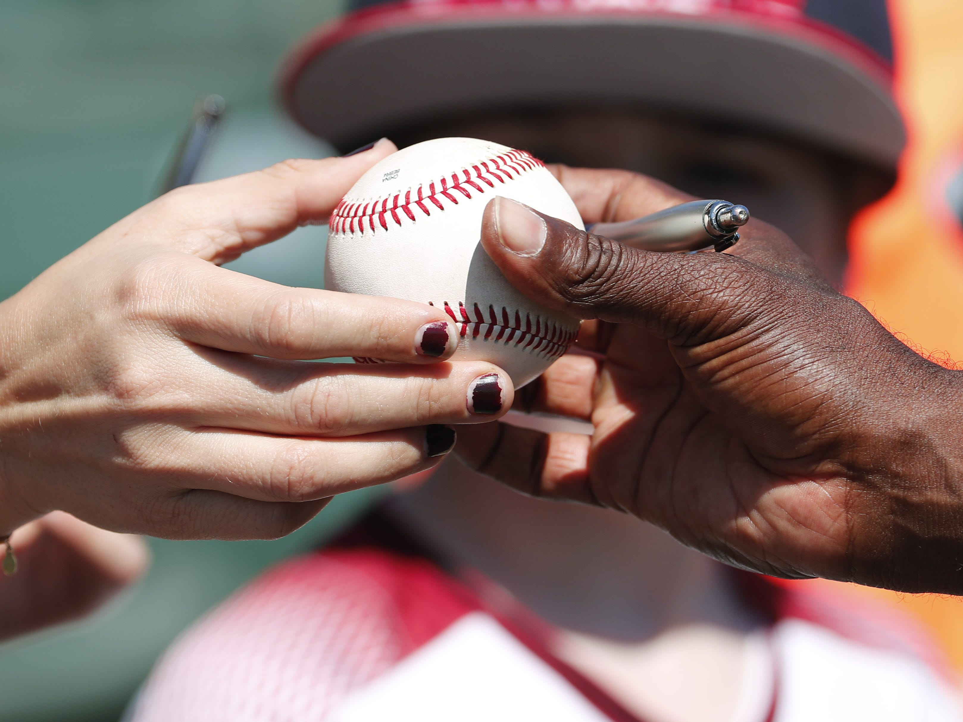 A fan gets a ball autographed before a spring training between the Arizona Diamondbacks and the Milwaukee Brewers at Salt River Fields at Talking Stick March 24, 2019.