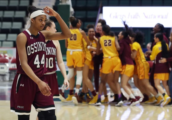 Ossining's Aubrey Griffin (44) and Alexandra Forman (30) walk off the court as Christ the King players celebrate after winning the championship game of the Federation Tournament at the Cool Insuring Arena in Glens Falls March 23, 2019.