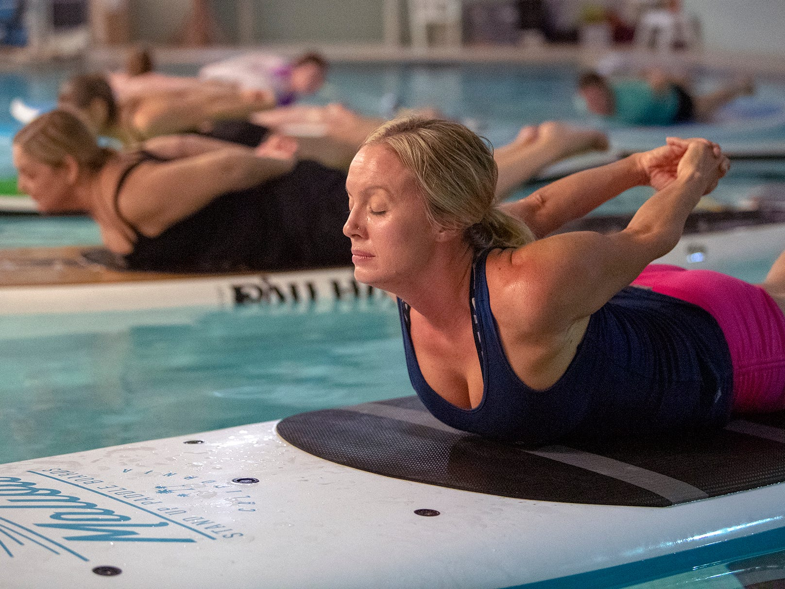 Heather Geare, a Yoga instructor for Shank's Mare and Stellar Fitness, leads the class on their paddle boards. The YWCA York is offering a Paddle Board Yoga Class in their pool for the first time. Shank's Mare provided the boards.