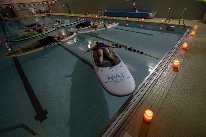 The lights are dimmed during a quiet moment at the end of the class. The YWCA York is offering a Paddle Board Yoga Class in their pool for the first time. Shank's Mare provided the boards. The class is offered on the open water in warmer weather.