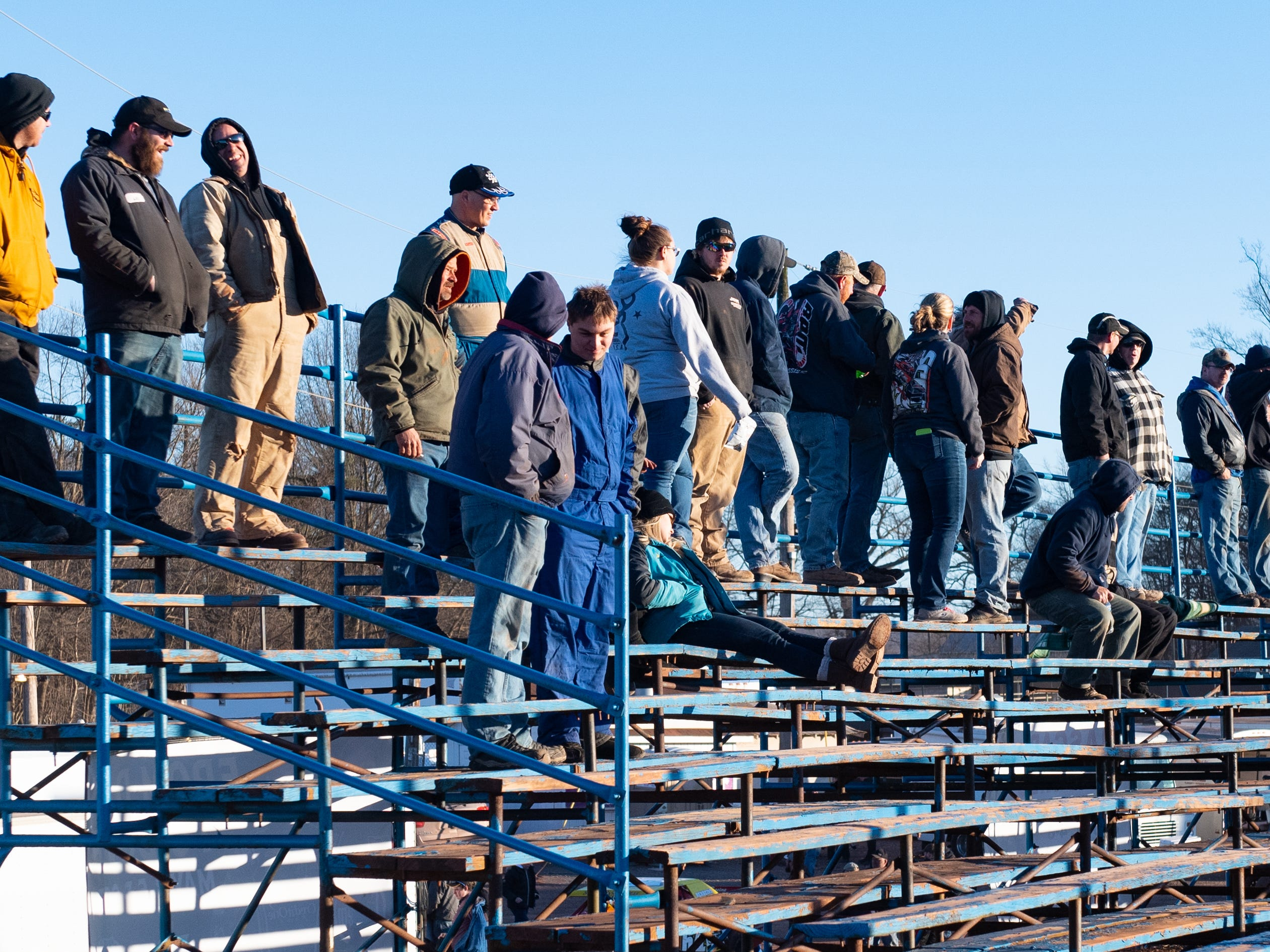 Spectators stand at the top of the bleachers to see over the fence during the 2019 season opener at BAPS Motor Speedway, March 23, 2019.
