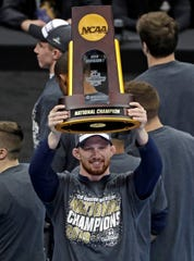 Penn State's Bo Nickal, who won his 197-pound match against Ohio State's Kollin Moore in the finals of the NCAA wrestling championships, holds the team championship trophy that Penn State school won for a record eighth time in nine years.