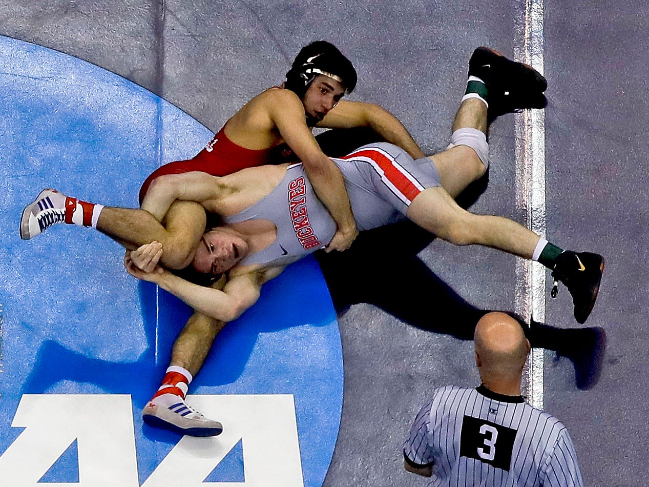 Cornell's Yianni Diakomihalis, top, and Ohio State's Joey McKenna work for control in their 141-pound match in the finals of the NCAA wrestling championships Saturday, March 23, 2019 in Pittsburgh. Diakomihalis, a Hilton graduate, won the match6-4 on a takedown in overtime.