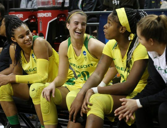 Oregon's Satou Sabally, left, Sabrina Ionescu, Ruthy Hebard and Taylor Chavez smile and talk on the bench near the end of the team's first-round game against Portland State in the NCAA women's college basketball tournament Friday, March 22, 2019, in Eugene, Ore. (AP Photo/Chris Pietsch)