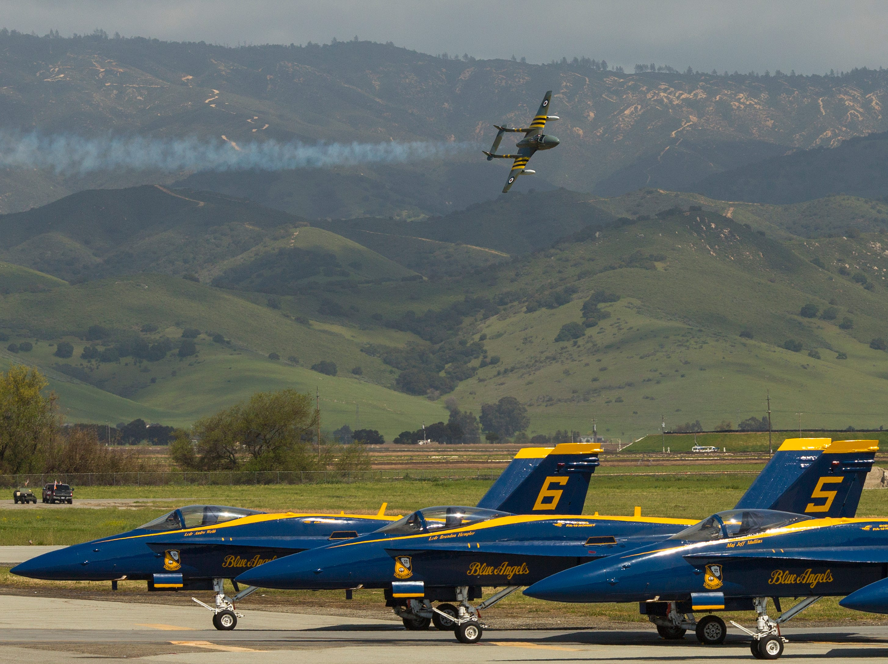 Jerry Conley flies his Vampire Jet above a row of parked Blue Angels F-18 jets during the California International Airshow Salinas at the Salinas Airport on March 23, 2019. (Photo by David Royal)