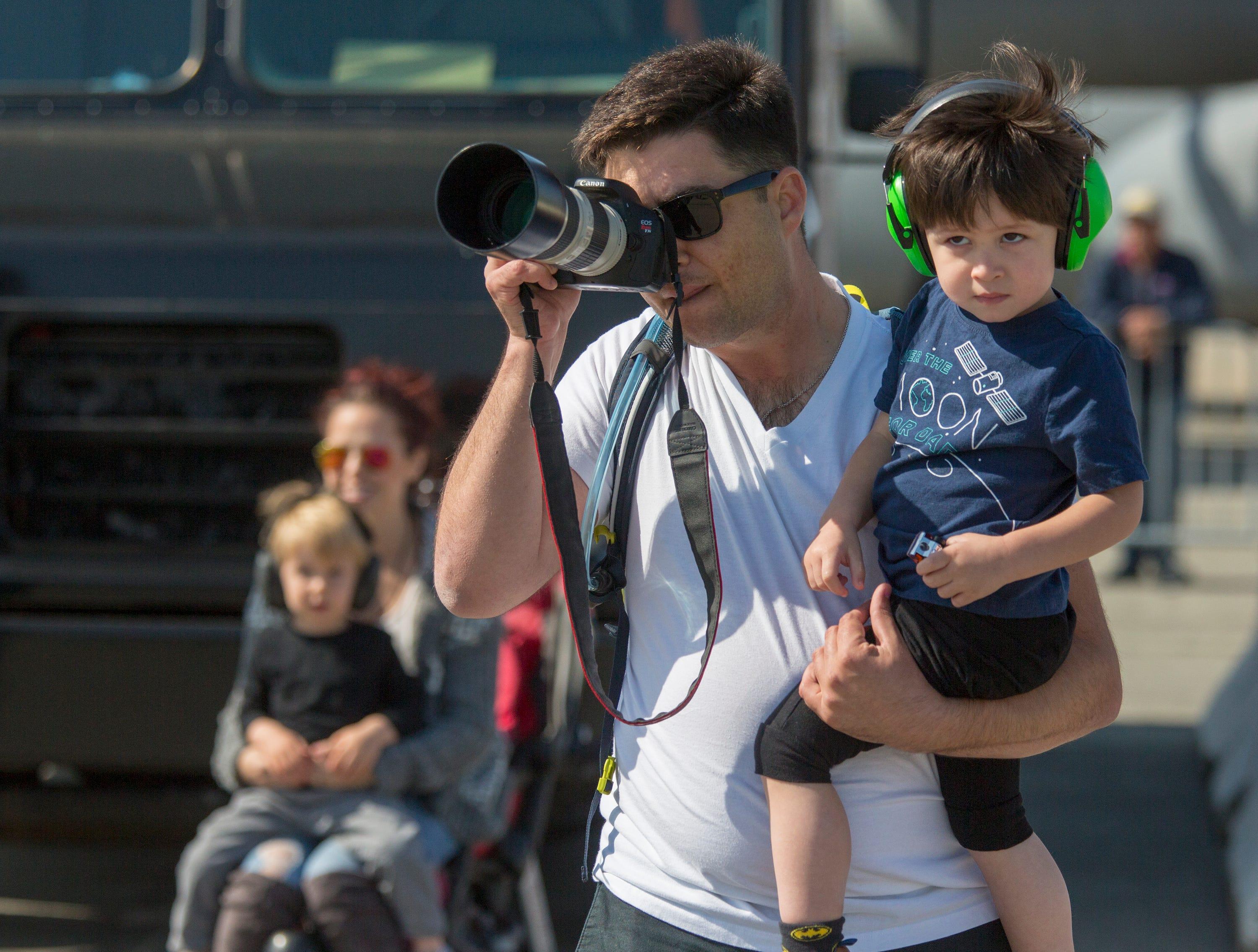 A man shoots photos while holding his son during the California International Airshow Salinas at the Salinas Airport on March 23, 2019. (Photo by David Royal)