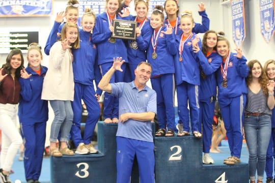The San Angelo Central girls gymnastics team and head coach Tony Walker celebrate winning an 18th straight district title at the Central gym on Saturday, March 23, 2019.