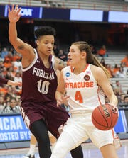Syracuse's Tiana Mangakahia (4) drives towards the basket as Fordham's Bre Cavanaugh defends during of a first-round game in the NCAA women's college basketball tournament in Syracuse, N.Y., Saturday, March 23, 2019. (AP Photo/Heather Ainsworth)
