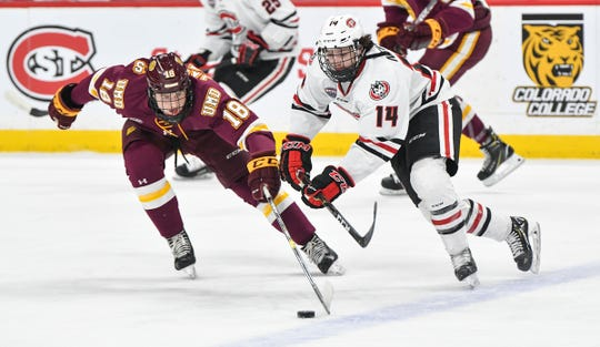 Patrick Newell of St. Cloud State (14) and Jesse Jacques of Minnesota-Duluth battle for control of the puck during the NCHC Frozen Faceoff championship game Saturday at the Xcel Energy Center in St. Paul, Minnesota.