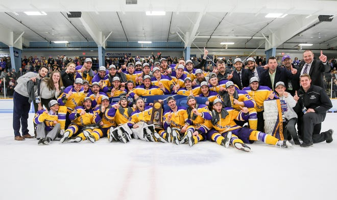 The UW-Stevens Point men's hockey team celebrates after winning the NCAA Division III national championship Saturday night.