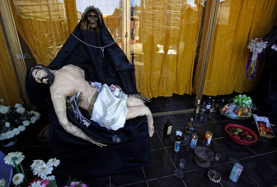 "In this March 1, 2017, file photo, a statue of La Santa Muerte, or ""Our Lady of Holy Death,"" holds a statue of Jesus on an altar inside a temple dedicated to Santa Muerte, on the outskirts Mexico City in the State of Mexico. Santa Fe Archbishop John Wester in Albuquerque, New Mexico, recently told The Associated Press he believes some Catholics may be fooled into venerating Santa Muerte even though the focus on death runs counter to the church's teachings and she's not an official Catholic saint."