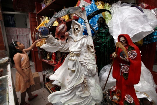"In this Feb. 19, 2017, file photo, a child arranges statues of La Santa Muerte, or ""Our Lady of Holy Death,""  on the edge of Mexico City's Tepito neighborhood.  A New Mexico archbishop is renewing his call for Catholics to stop worshipping the skeleton folk saint, saying he fears some mistakenly believe the Grim Reaper-like figure is a Roman Catholic Church-sanctioned saint. Santa Fe Archbishop John Wester recently told The Associated Press he believes some Catholics may be fooled into venerating Santa Muerte even though the focus on death runs counter to the church's teachings."
