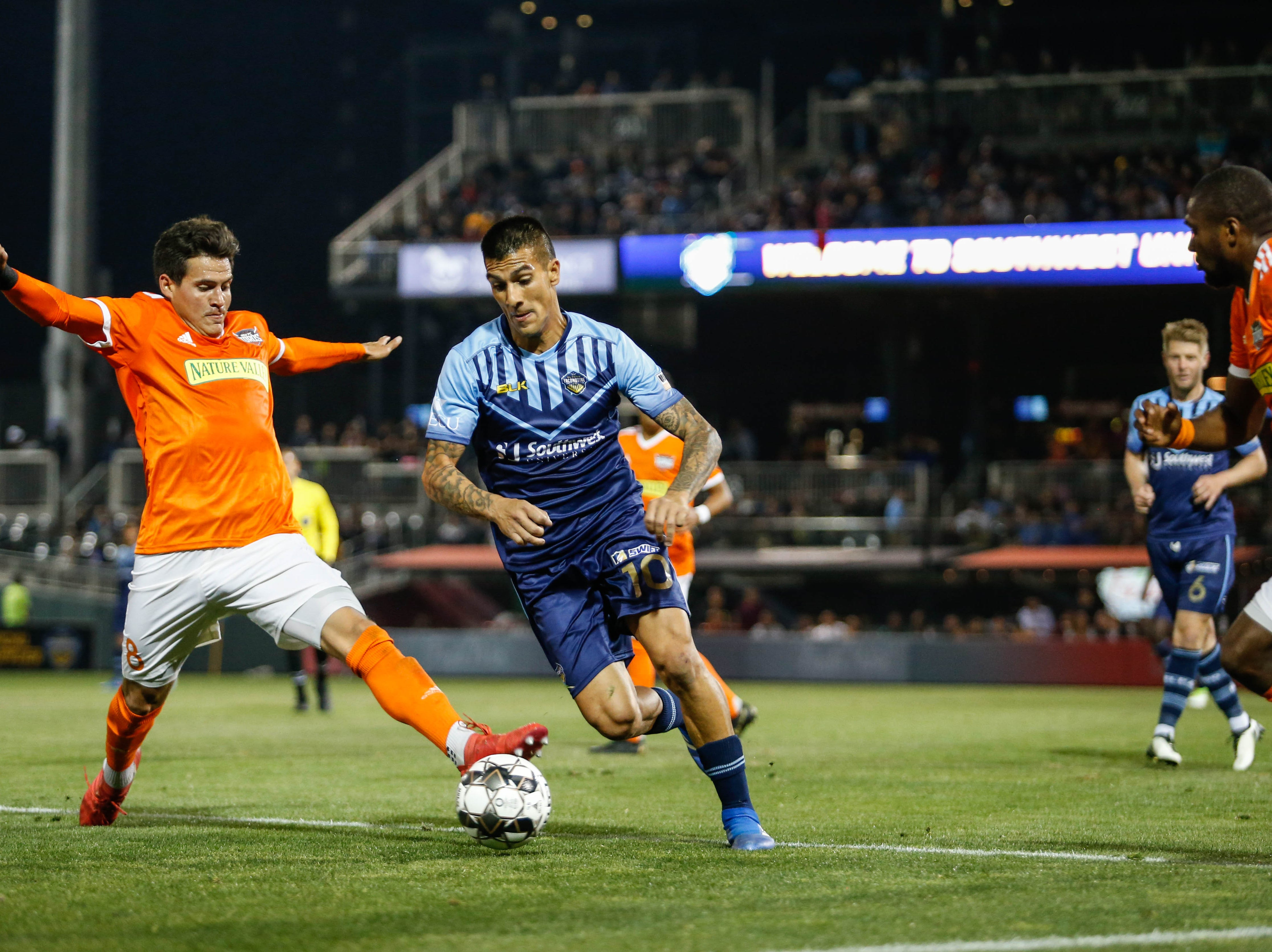 El Paso Locomotive midfielder Sebastián Contreras, center, moves the ball forward.