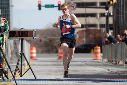 Third-time Caesar Rodney Half-Marathon champ Nate Alter crosses the finish line to win the Caesar Rodney Half Marathon Sunday morning in Wilmington. Alter finished with a time of 1:11:07.9.