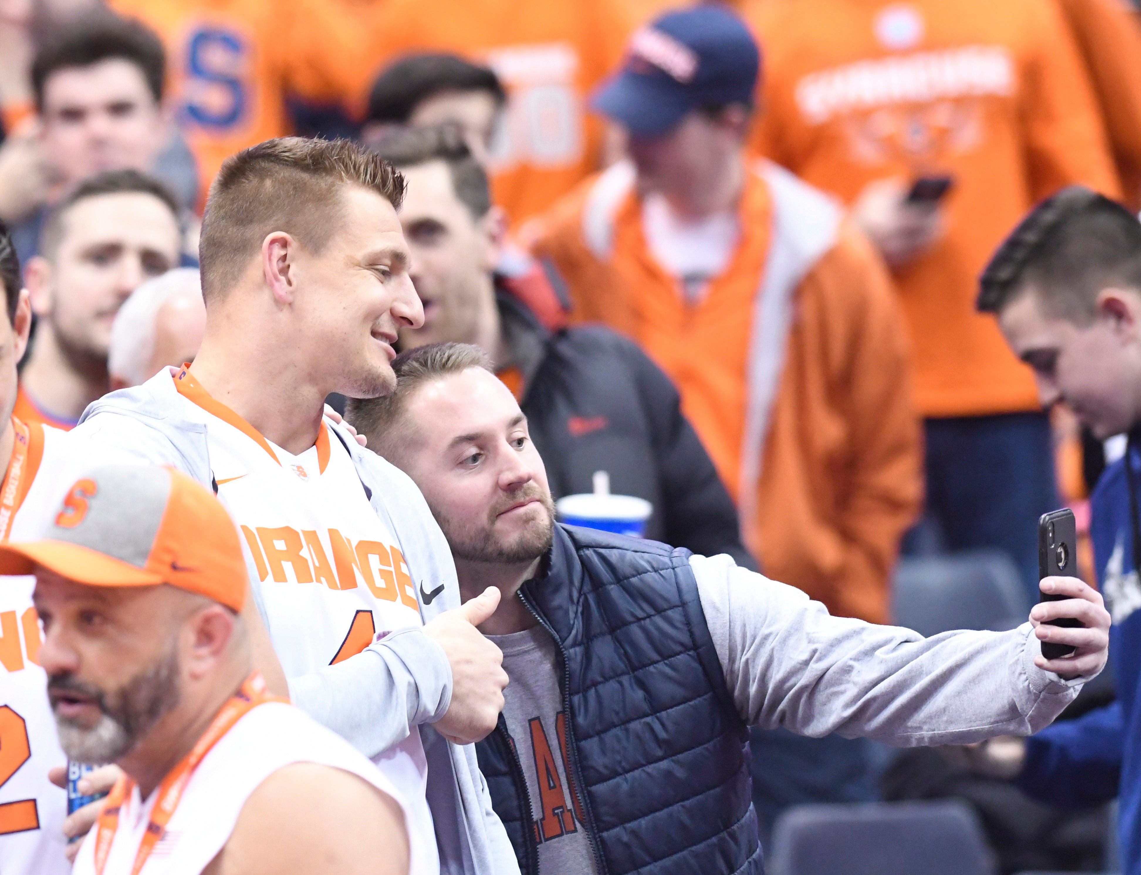 Feb. 23, 2019: Rob Gronkowski poses with a fan for a selfie prior to a men's basketball game between Syracuse and Duke at the Carrier Dome.