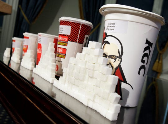 A display showing how much sugar is contained in various fast-food soft drinks.