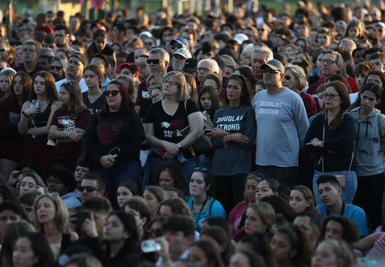 People attend a memorial service FEb. 14, 2019 in Parkland, Florida, to mark the first anniversary of the shooting at Marjory Stoneman Douglas High School.